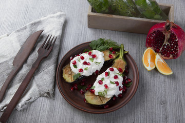 baked eggplants on a plate with cream cheese and pomegranate seeds