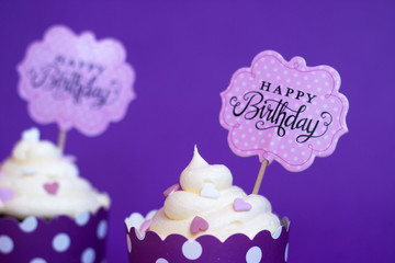 Vanilla cupcakes with small decorative hearts and happy birthday sign, against violet background; party background