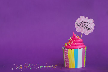 Tasty strawberry cupcake with sprinkles and Happy Birthday banner on violet background. Party background