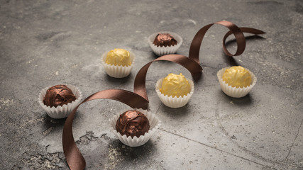 Chocolate sweets of various kinds of round forms are decorated with a silk ribbon on a gray background. Festive concept. Horizontal frame