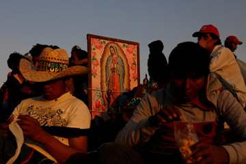 Pilgrims rest beside an image of the Virgin of Guadalupe at the Basilica of Guadalupe during the annual pilgrimage in honor of the Virgin of Guadalupe, patron saint of Mexican Catholics, in Mexico City,