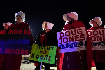 """Women dressed as characters from """"The Handmaid's Tale"""" protest at the exit gate after a Republican Senate candidate Roy Moore campaign rally in Midland City, Alabama"""