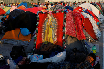 Pilgrims rest beside an image of the Virgin of Guadalupe at an improvised camp site at the Basilica of Guadalupe during the annual pilgrimage in honor of the Virgin of Guadalupe, patron saint of Mexican Catholics, in Mexico