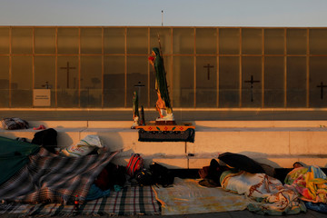 Pilgrims sleep beside an image of the Virgin of Guadalupe at an improvised camp site at the Basilica of Guadalupe during the annual pilgrimage in honor of the Virgin of Guadalupe, patron saint of Mexican Catholics, in Mexico City