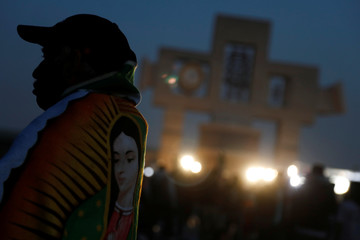 A pilgrim wears an image of the Virgin of Guadalupe during the annual pilgrimage in honor of the Virgin of Guadalupe, patron saint of Mexican Catholics, in Mexico City