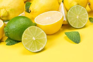 on a yellow wooden table, sliced lemons and lime together with mint leaves