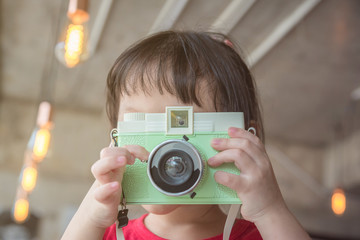 Young asian girl taking photo by classic camera