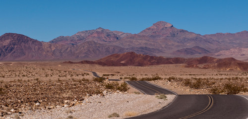 A desert road in California with a beautiful mountain range in the distance