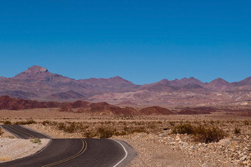 A desert road in the California desert with a beautiful mountain range in the distance