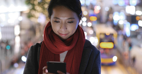 Woman use of smart phone in city over traffic background