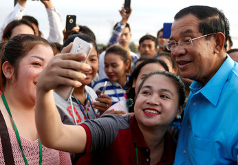 A garment worker takes a selfie with Cambodia's Prime Minister Hun Sen on the outskirts of Phnom Penh