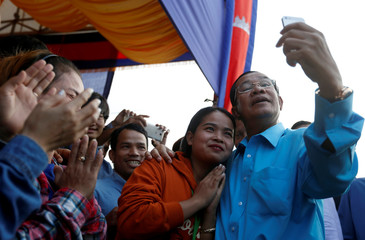Cambodia's Prime Minister Hun Sen takes a selfie with garment workers before a meeting on the outskirts of Phnom Penh