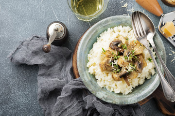 Risotto with chicken and mushrooms, thyme, garlic, parmesan cheese on old gray concrete background. Traditional Italian dish. Selective focus. Rustic style. Top view.
