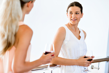 Young woman with her friend holding a glass of wine indoors