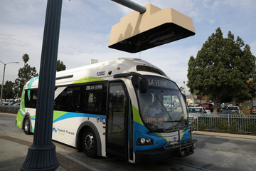 An electric bus sits under a charging station in Pomona
