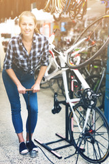 Female master is standing with pump for bicycle