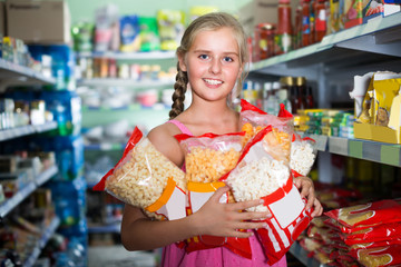 Teenage girl is standing with packets of popcorn