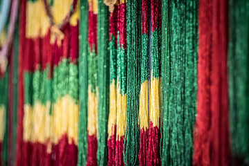 Colored strings of green, yellow and red beads on street market