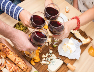 Frends eating cheese with grapes and drinking wine at home together, cheese party concept.