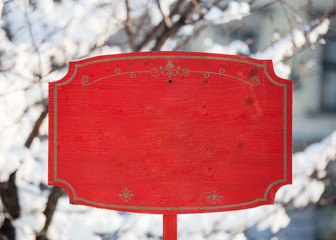 Red holiday Christmas wooden sign mockup empty placeholder entrance exit New Year Santa holiday market in the park during winter snow trees