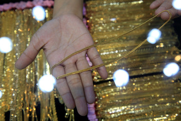 Employee shows gold necklace to customer at a jewellery shop in Jakarta