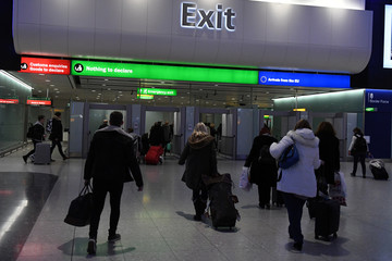 People walk through the customs exit at Heathrow airport in London