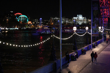 A couple walk on the South Bank at night in London