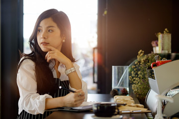 Portrait of asian young woman cafe owner writing notebook.