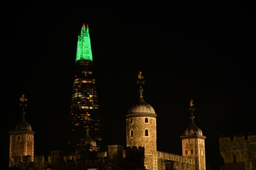The top of the Shard building, illuminated to resemble a Christmas tree, is seen behind the Tower of London