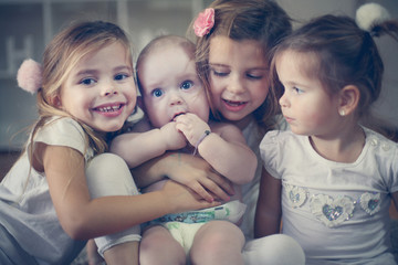 Little baby brother poses to camera with little sisters.