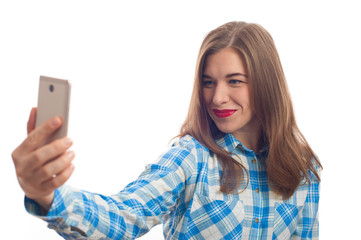Portrait of a smiling cute woman wearing plaid shirt making selfie photo on smartphone on a white background