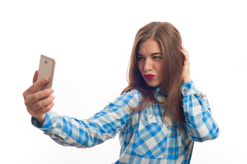 Happy beautiful young woman standing and making selfie picture using her smartphone. Attractive female wearing plaid shirt posing over white background.
