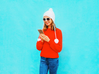 Fashion smiling young woman is using smartphone in red sweater, hat on a blue background