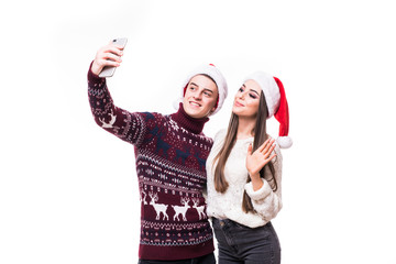 happy couple in santa hats taking selfie picture with smart-phone on white background.