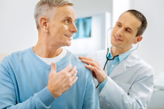 Being optimistic. Cheerful delighted positive man smiling and turning to his doctor while feeling optimistic