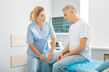 Professional treatment. Positive friendly nice therapist standing near her patient and talking to him while checking his leg