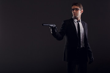 Image of man in glasses and leather gloves with gun