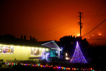 People stand on a roof of a home illuminated with Christmas lights to watch wildfire on a hillside burn during the Thomas Fire in Santa Barbara county near Carpinteria