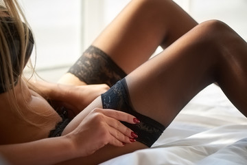 Woman putting on stocking. Female legs in bed.