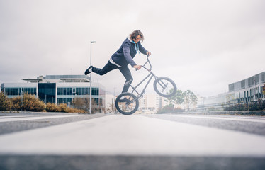 Young man practices with BMX bicycle.