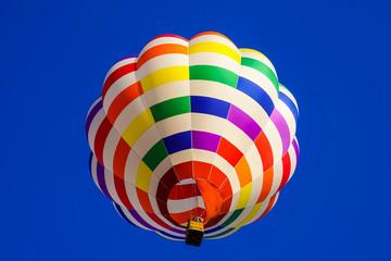 雲のない青空に舞うレインボーカラーのカラフルな熱気球 1機 青空背景