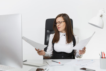Beautiful tired perplexed and stress brown-hair business woman in suit and glasses sitting at the desk, working at contemporary computer with documents in light office on white background