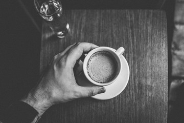 Man's hand holding coffee cup on wooden table in black and white