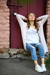 Resting woman teenage hippie stylish sitting in beautiful place street lifestyle momet