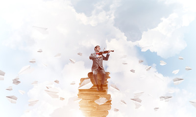Handsome violinist play his melody and paper planes fly around