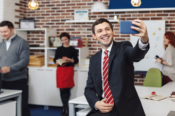 Smiling happy businessman making a selfie while his colleagues a