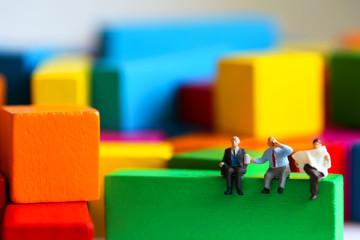 Miniature people : businessman sitting on wood color block