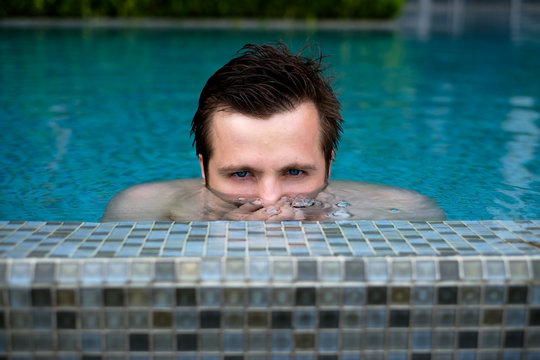 Young caucasian man swimming and lurking on summer vacation at pool. Half head above water stalking.