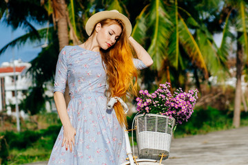 Beautiful red hair woman in a dress resting near a bicycle