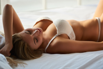 Beautiful woman in bed. Sexy girl with eyes closed.